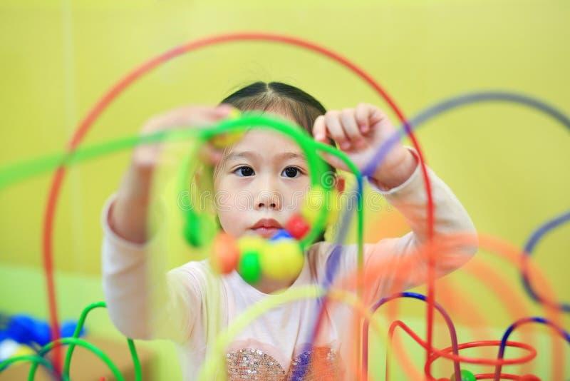 Ασιατικό κορίτσι παιδιών κινηματογραφήσεων σε πρώτο πλάνο που παίζει το εκπαιδευτικό παιχνίδι για την ανάπτυξη εγκεφάλου στο δωμά στοκ εικόνες