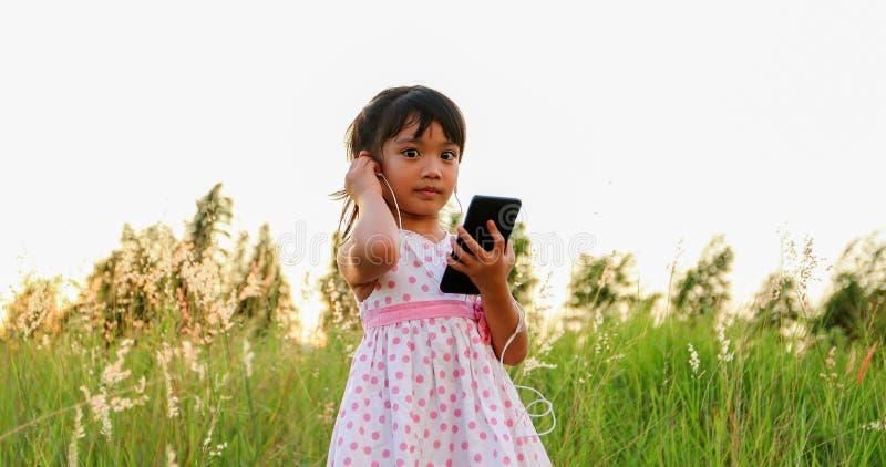 Ασιατικό κορίτσι παιδιών που ακούει τη μουσική και που τραγουδά από ένα κινητό τηλέφωνο και ευτυχές στο λιβάδι το καλοκαίρι στη φ στοκ εικόνες