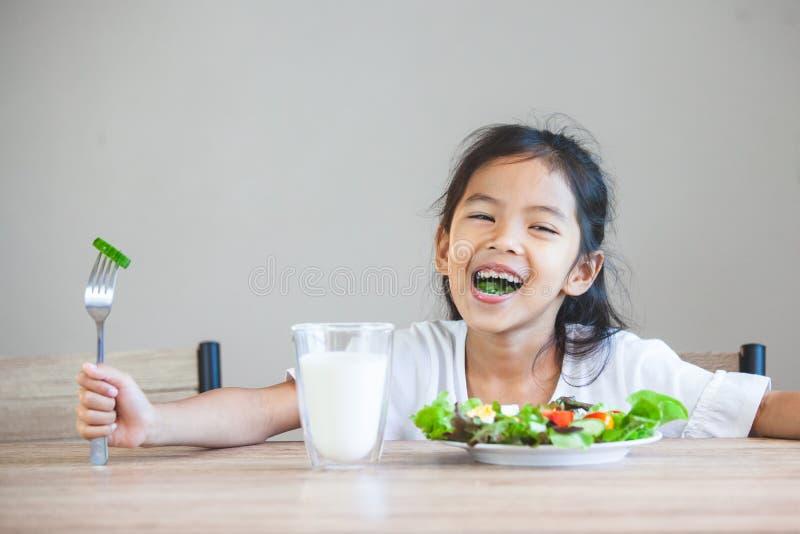 Ασιατικό κορίτσι παιδιών που τρώει τα υγιή λαχανικά και το γάλα για το γεύμα της στοκ εικόνες