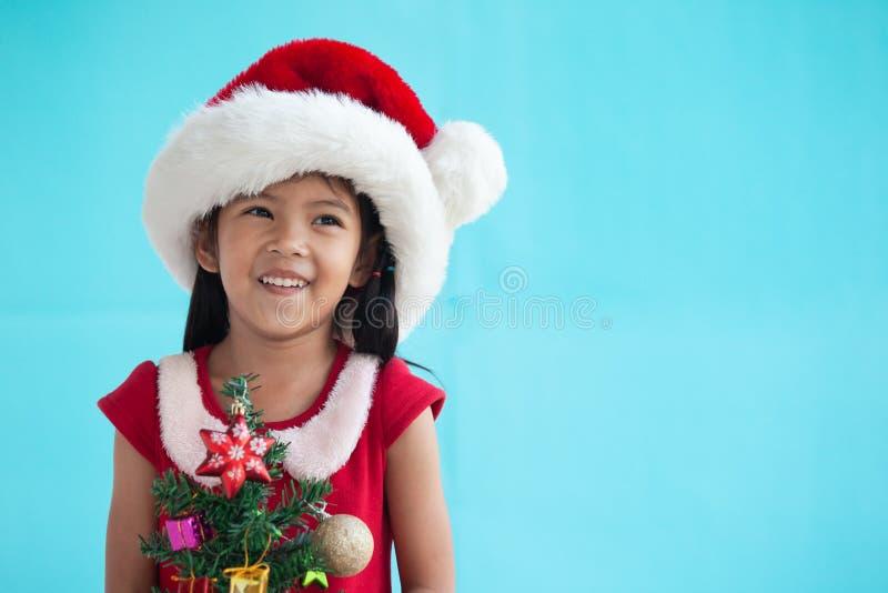 Ασιατικό κορίτσι παιδιών που φορά το καπέλο santa και που κρατά το χριστουγεννιάτικο δέντρο στοκ φωτογραφίες