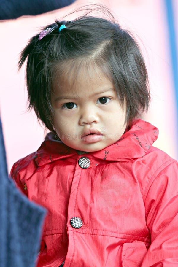 Ασιατικό κορίτσι παιδιών μωρών στο κόκκινο που ντύνεται. στοκ φωτογραφίες