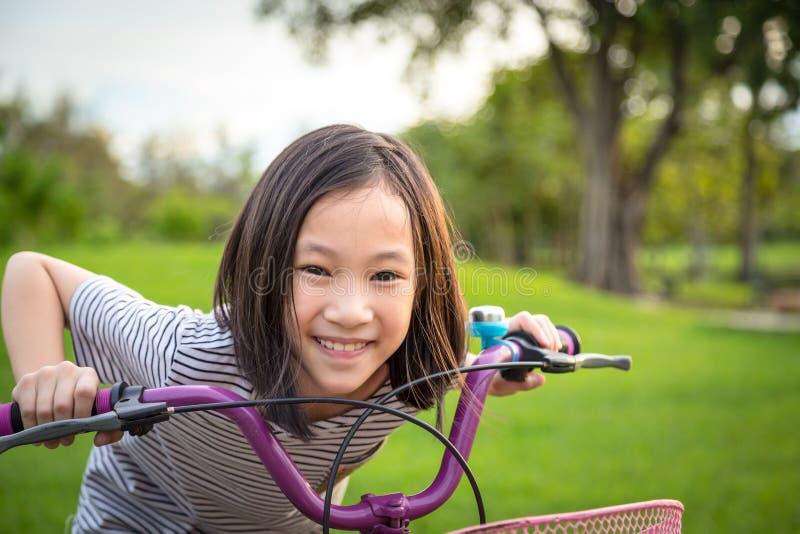 Ασιατικό κορίτσι που εξετάζει τη κάμερα, που χαμογελά με έναν χαριτωμένο στο ποδήλατο στο υπαίθριο πάρκο, άσκηση παιδιών στη φύση στοκ εικόνα