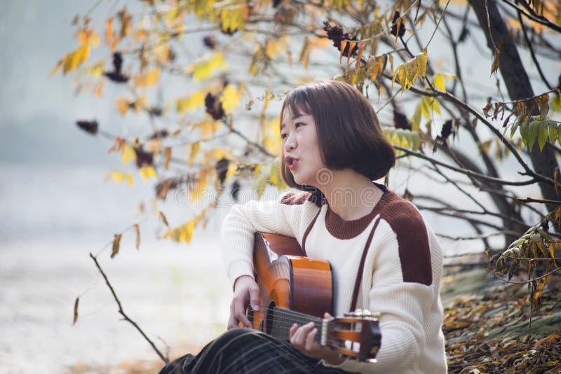Ασιατικό κορίτσι που παίζει την κιθάρα μουσικός χωρών δυτικός στοκ φωτογραφίες με δικαίωμα ελεύθερης χρήσης