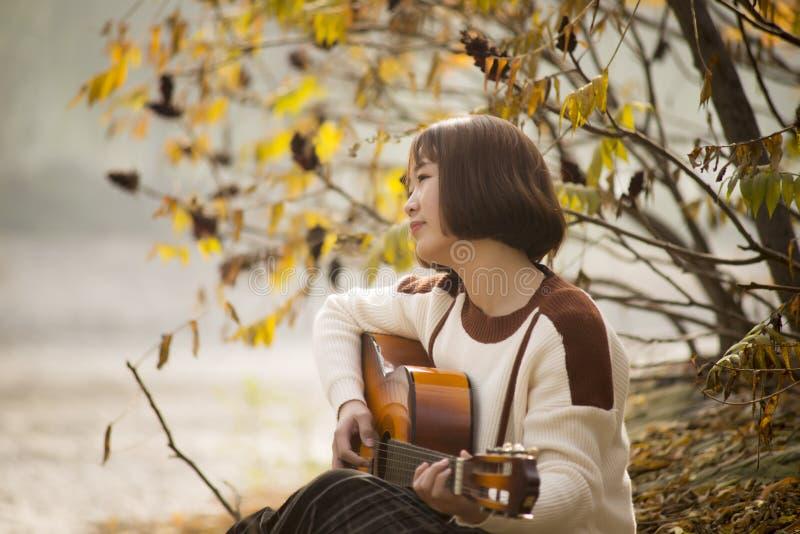 Ασιατικό κορίτσι που παίζει την κιθάρα μουσικός χωρών δυτικός στοκ εικόνες