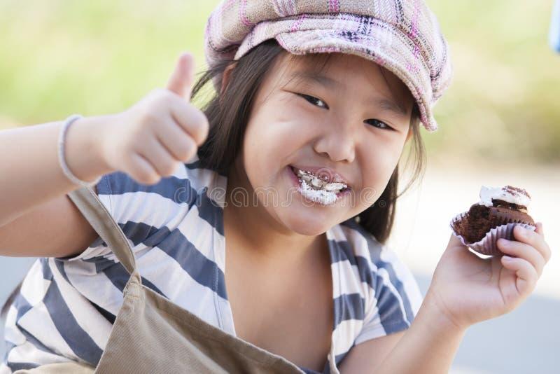 Ασιατικό κορίτσι που τρώει cupcake στοκ εικόνες