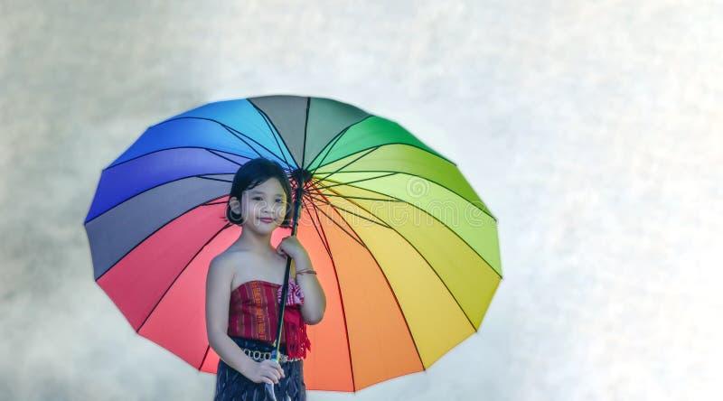 Ασιατικό μικρό κορίτσι με τη ζωηρόχρωμη ομπρέλα στοκ εικόνες
