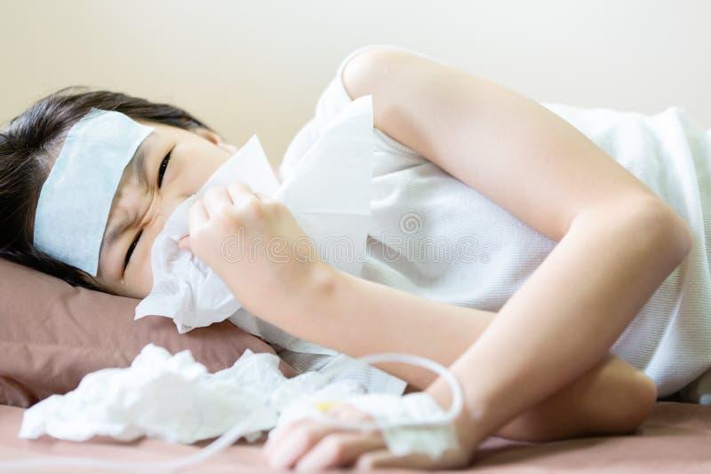 Ασιατικό μικρό κορίτσι που φυσά τη μύτη της σε έναν ιστό με το κρύο πήκτωμα που τοποθετείται στο μέτωπό της, αλλεργική ρινίτιδα,  στοκ εικόνα
