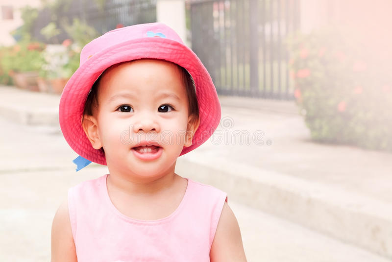 Ασιατικό μικρό κορίτσι στο ρόδινα καπέλο και το φόρεμα στοκ εικόνες με δικαίωμα ελεύθερης χρήσης