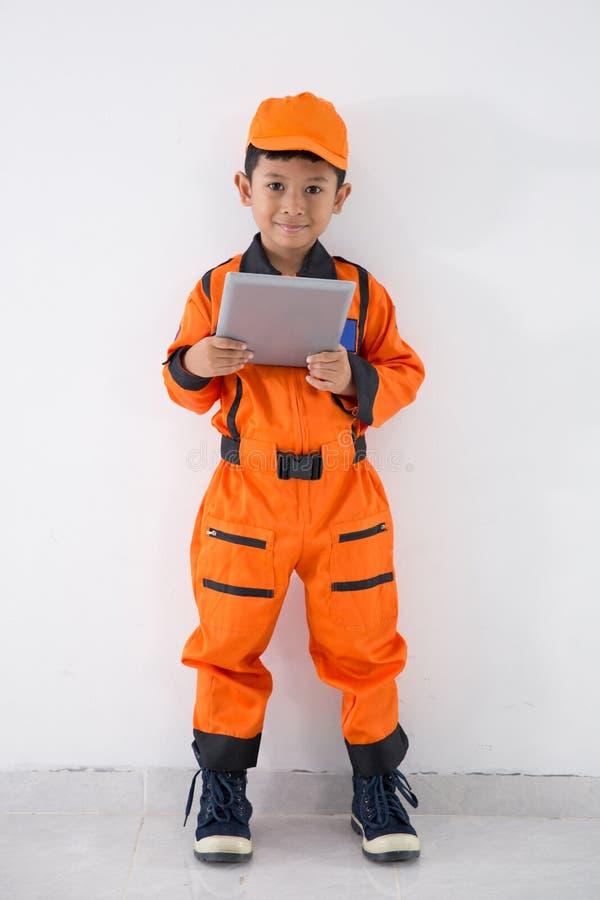 Ασιατικό μικρό παιδί με τον τεχνικό, το μηχανικό ή τον αστροναύτη ομοιόμορφους στοκ εικόνα με δικαίωμα ελεύθερης χρήσης