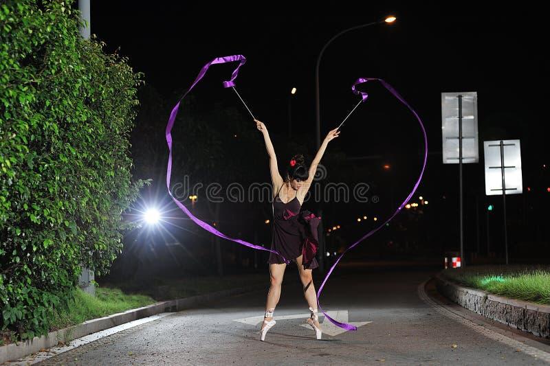 Ασιατικό μπαλέτο χορού κοριτσιών στο δρόμο τη νύχτα στοκ φωτογραφία