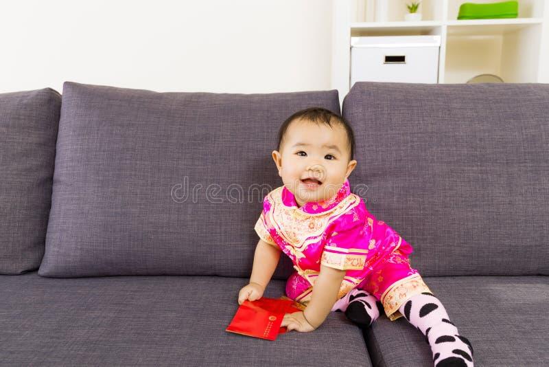Ασιατικό μωρό που κρατά την κόκκινη τσέπη με τον ιματισμό παραδοσιακού κινέζικου στοκ εικόνες