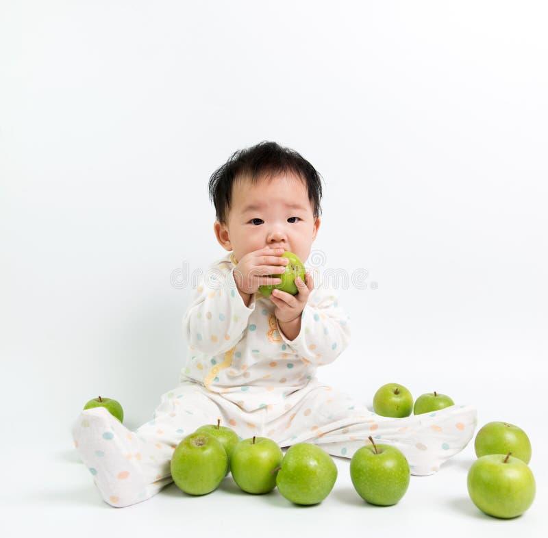 Ασιατικό μωρό που τρώει το πράσινο μήλο στοκ εικόνα με δικαίωμα ελεύθερης χρήσης