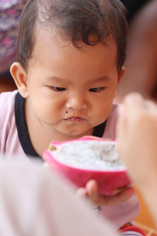 Ασιατικό μωρό που τρώει φρούτα δράκων με ευτυχώς στοκ εικόνα με δικαίωμα ελεύθερης χρήσης