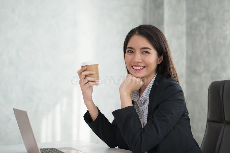 Ασιατικό νέο επιχειρησιακό κορίτσι που κρατά ένα φλυτζάνι καφέ διαθέσιμο, κάθισμα στοκ φωτογραφία