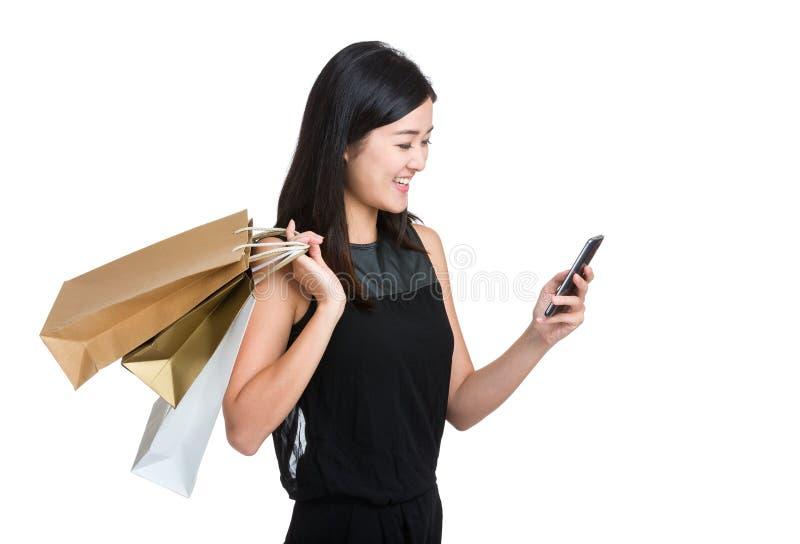 Ασιατικό νέο κινητό τηλέφωνο χρήσης γυναικών με την τσάντα αγορών στοκ φωτογραφίες