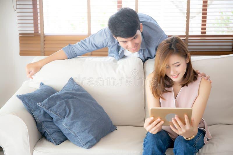Ασιατικό νεαρό ζευγάρι χαλαρώνει κοιτώντας την ψυχαγωγία στο διαδίκτυο μαζί στον καναπέ στο σπίτι, στην οικογένεια στοκ εικόνες
