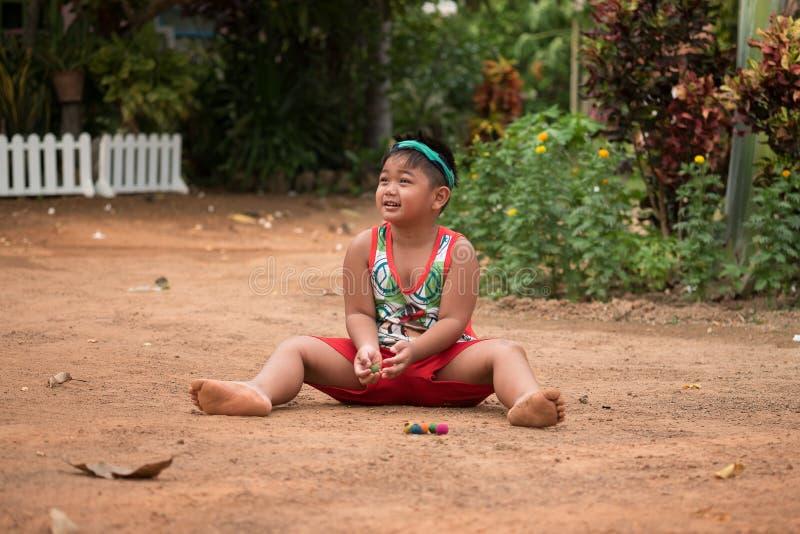 Ασιατικό παιχνίδι παιδιών με την άμμο και τη σφαίρα στην παιδική χαρά στοκ εικόνες