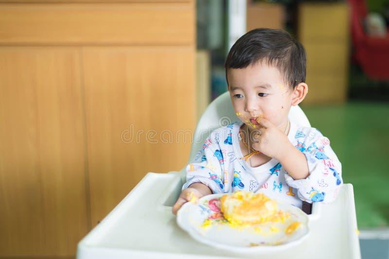 Ασιατικό παιδί που τρώει το κέικ γενεθλίων με την κρέμα στο πρόσωπο στοκ φωτογραφία