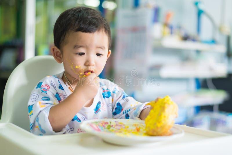 Ασιατικό παιδί που τρώει το κέικ γενεθλίων με την κρέμα στο πρόσωπο στοκ εικόνες με δικαίωμα ελεύθερης χρήσης