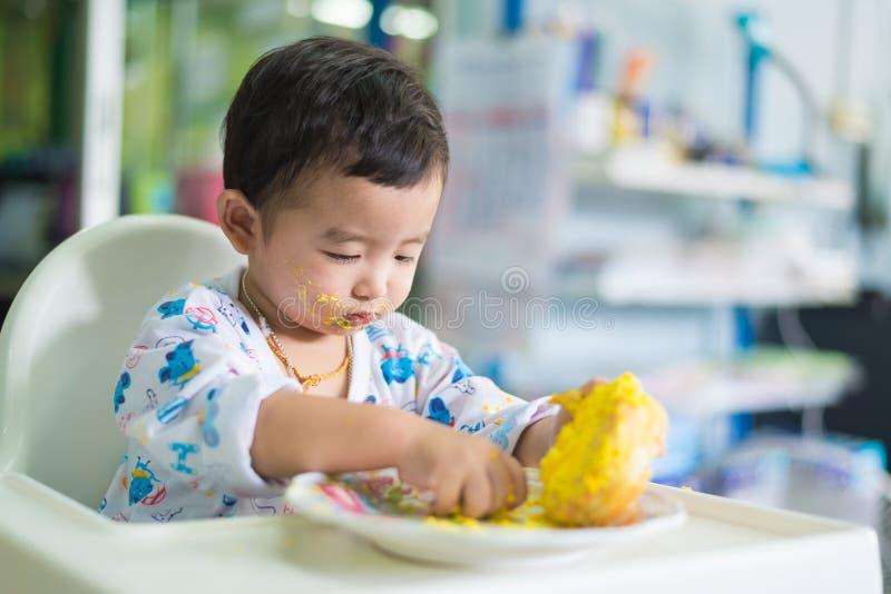 Ασιατικό παιδί που τρώει το κέικ γενεθλίων με την κρέμα στο πρόσωπο στοκ φωτογραφία με δικαίωμα ελεύθερης χρήσης