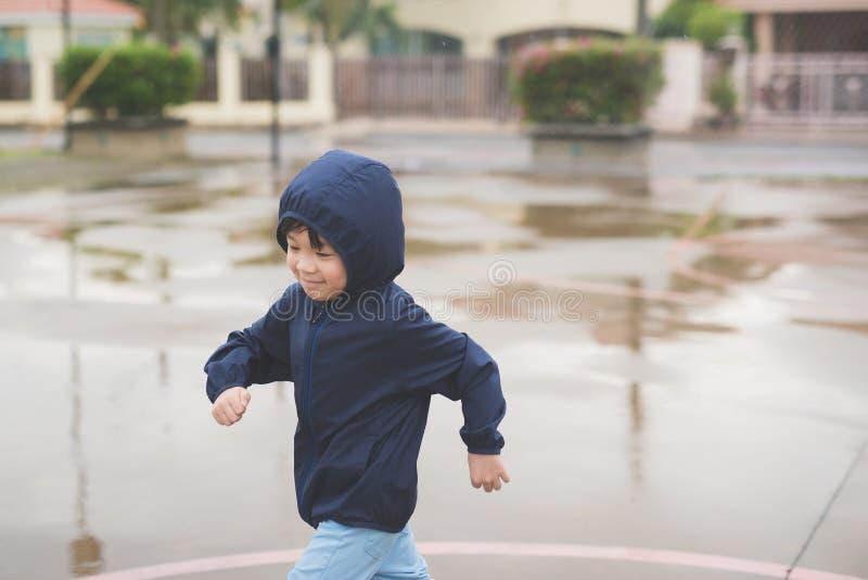 Ασιατικό παιδί στο μπλε αδιάβροχο στοκ εικόνα