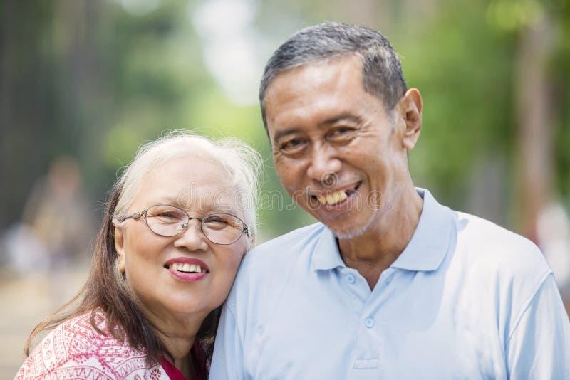 Ασιατικό παλαιό ζεύγος που χαμογελά στη κάμερα στοκ εικόνες