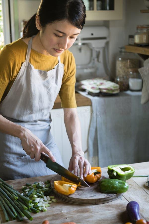 Ασιατικό πολυάσχολο μαγείρεμα γυναικών στην κουζίνα στοκ φωτογραφία με δικαίωμα ελεύθερης χρήσης