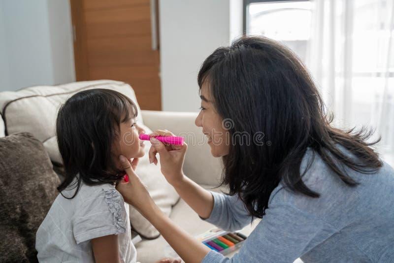 Ασιατικό πρόσωπο μητέρων που χρωματίζει την λίγη κόρη στοκ φωτογραφία με δικαίωμα ελεύθερης χρήσης