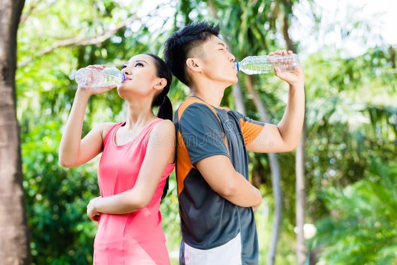 Ασιατικό πόσιμο νερό ζευγών μετά από τον αθλητισμό στο πάρκο στοκ εικόνες