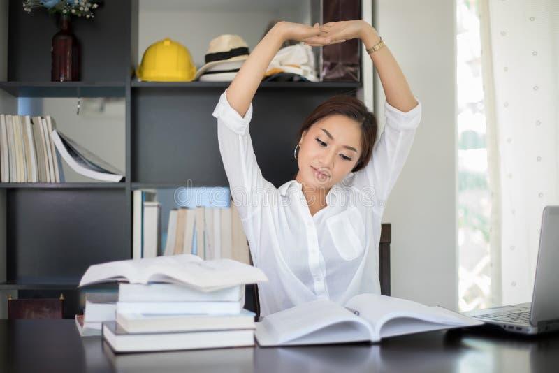 Ασιατικό τέντωμα γυναικών στον εργασιακό χώρο της και χαμόγελο στο offic στοκ εικόνες