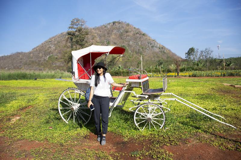 Ασιατικό ταϊλανδικό ταξίδι γυναικών και τοποθέτηση με την κλασική εκλεκτής ποιότητας δίτροχο χειράμαξα ποδηλάτων σε υπαίθριο με τ στοκ εικόνες