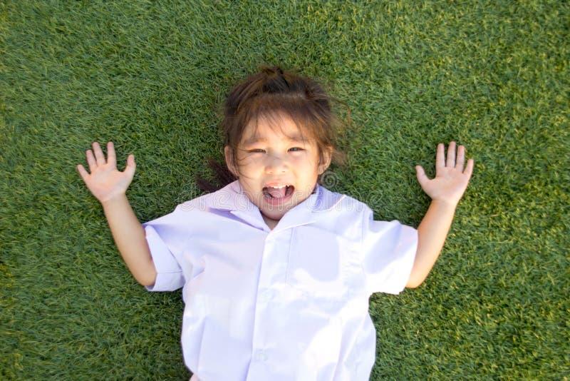 ασιατικό ταϊλανδικό χαμόγελο παιδιών στην πράσινη χλόη στοκ εικόνα