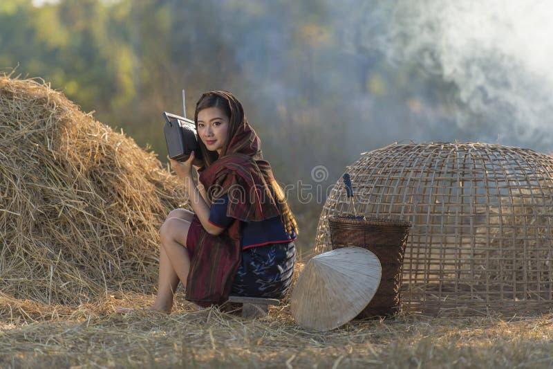 Ασιατικό τοπικό όμορφο ραδιόφωνο ακούσματος γυναικών στο άχυρο στοκ φωτογραφίες με δικαίωμα ελεύθερης χρήσης