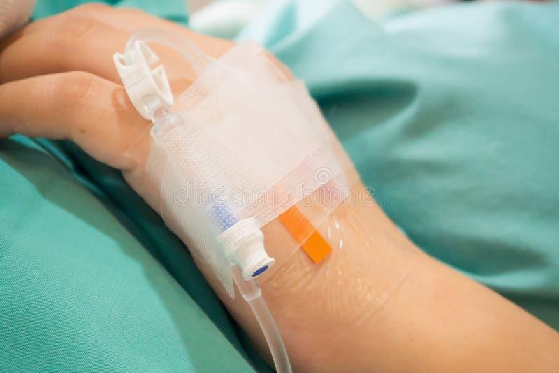 Ασιατικό υπομονετικό χέρι γυναικών σε IV σταλαγματιά με την αλατούχο λύση, ρευστό στοκ φωτογραφία με δικαίωμα ελεύθερης χρήσης