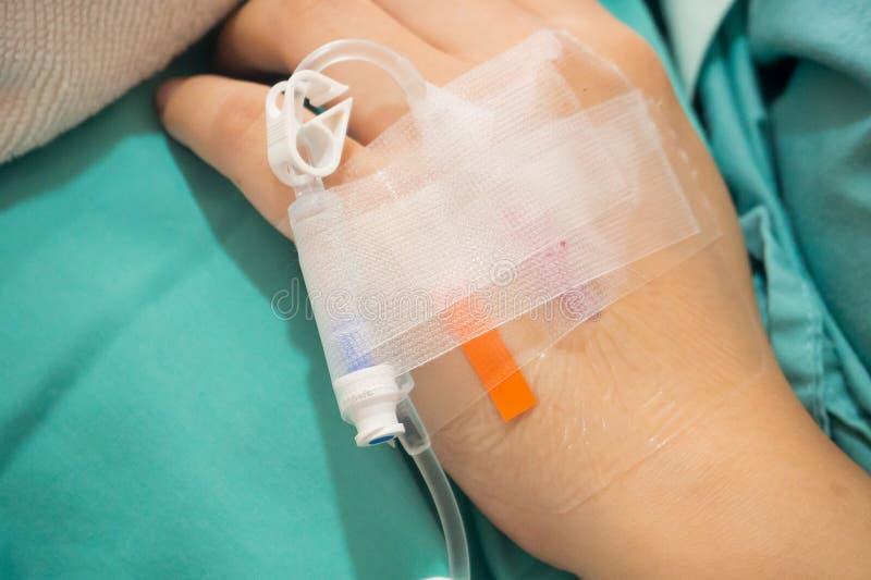 Ασιατικό υπομονετικό χέρι γυναικών σε IV σταλαγματιά με την αλατούχο λύση, ρευστό στοκ εικόνες