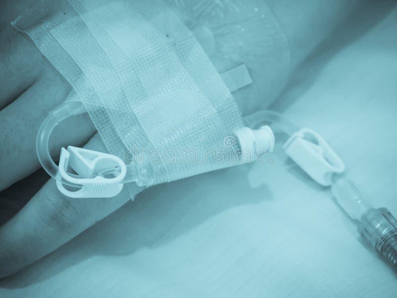 Ασιατικό υπομονετικό χέρι γυναικών σε IV σταλαγματιά με την αλατούχο λύση, στοκ εικόνα