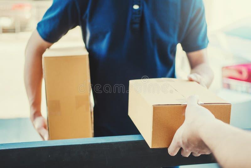 Ασιατικό χέρι ατόμων έννοιας παράδοσης που δέχεται τα κιβώτια μιας παράδοσης από επαγγελματικό deliveryman στο σπίτι στοκ εικόνα