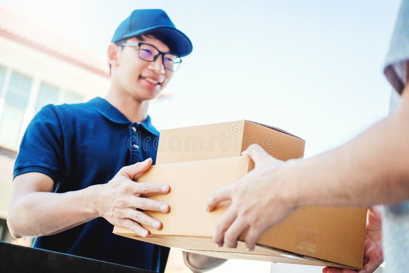 Ασιατικό χέρι ατόμων έννοιας παράδοσης που δέχεται τα κιβώτια μιας παράδοσης από επαγγελματικό deliveryman στο σπίτι στοκ φωτογραφία