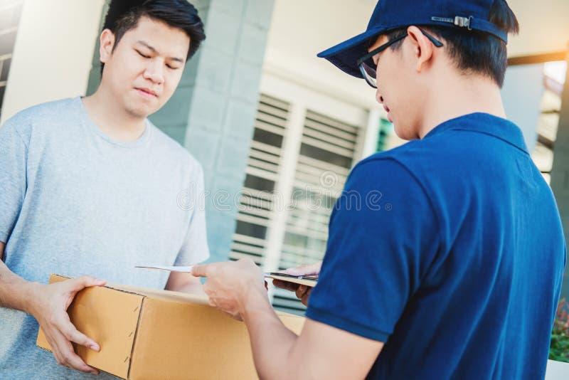 Ασιατικό χέρι ατόμων έννοιας παράδοσης που δέχεται τα κιβώτια μιας παράδοσης από επαγγελματικό deliveryman στο σπίτι στοκ φωτογραφίες