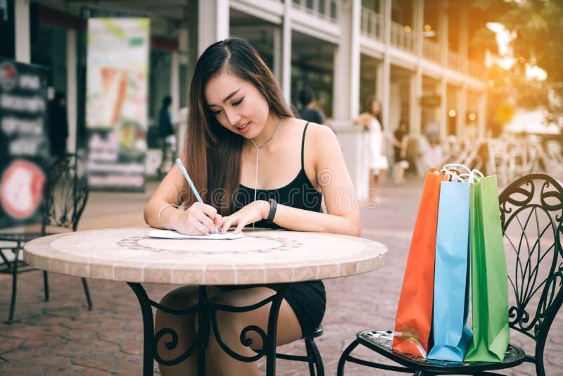 Ασιατικό χέρι γυναικών που ελέγχει τον κατάλογο αγορών στο γραφείο στην εξωτερική λεωφόρο εξόδου στοκ φωτογραφίες