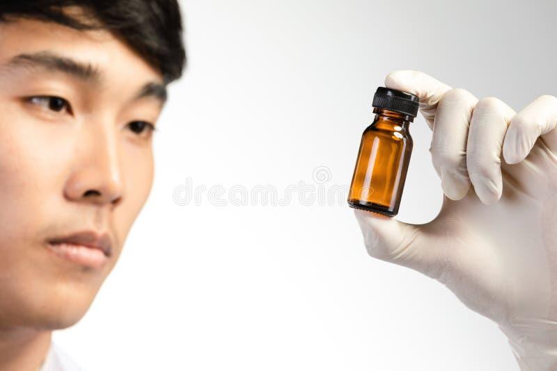 Ασιατικό χέρι επιστημόνων που κρατά το κενό μικρό καφετί μπουκάλι ιατρικής στοκ εικόνα με δικαίωμα ελεύθερης χρήσης
