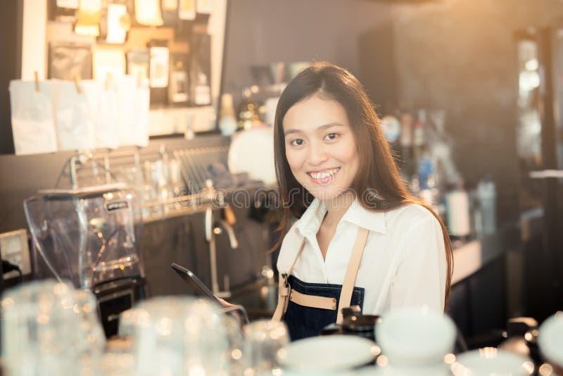 Ασιατικό barista γυναικών που χαμογελά με την ταμπλέτα στο χέρι της στοκ εικόνες