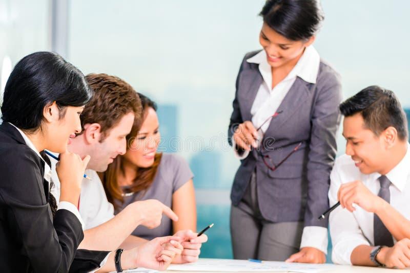 Ασιατικό Businesspeople που διοργανώνει τη συνεδρίαση στην αρχή στοκ εικόνες