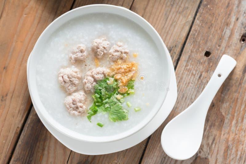 Ασιατικό congee με το κομματιασμένο χοιρινό κρέας στο άσπρο κύπελλο Τοπ όψη στοκ εικόνα