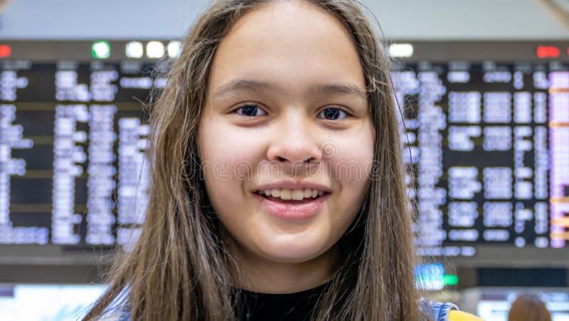 Ασιατικό tween κορίτσι μπροστά από τον πίνακα αφίξεων αερολιμένων στοκ φωτογραφίες