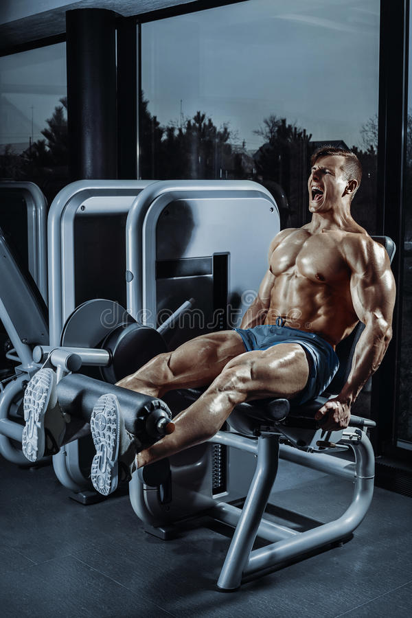 Ασκήσεις ποδιών - άτομο που κάνει το πόδι με τη μηχανή στη γυμναστική στοκ εικόνα με δικαίωμα ελεύθερης χρήσης