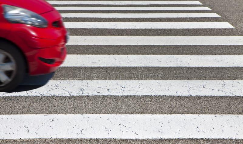 Ασπρόμαυρος πεζός που διασχίζει με κόκκινο αυτοκίνητο στο φόντο - εικόνα με χώρο αντιγραφής - Το σχήμα του αυτοκινήτου έχει τροπο στοκ εικόνες με δικαίωμα ελεύθερης χρήσης