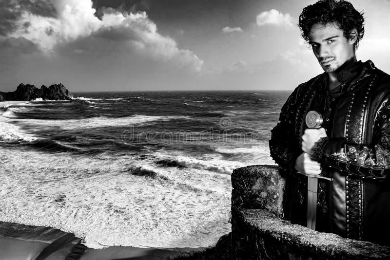 Ασπρόμαυρο πορτρέτο του ιππότη που στέκεται στο μπαλκο του κάστρου με σπαθί και κοιτάζει την κάμερα με ωκεανούς στοκ φωτογραφία με δικαίωμα ελεύθερης χρήσης