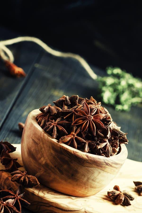 Αστέρια γλυκάνισου σε ένα ξύλινο κύπελλο, σκοτεινό υπόβαθρο, εκλεκτική εστίαση στοκ εικόνα με δικαίωμα ελεύθερης χρήσης