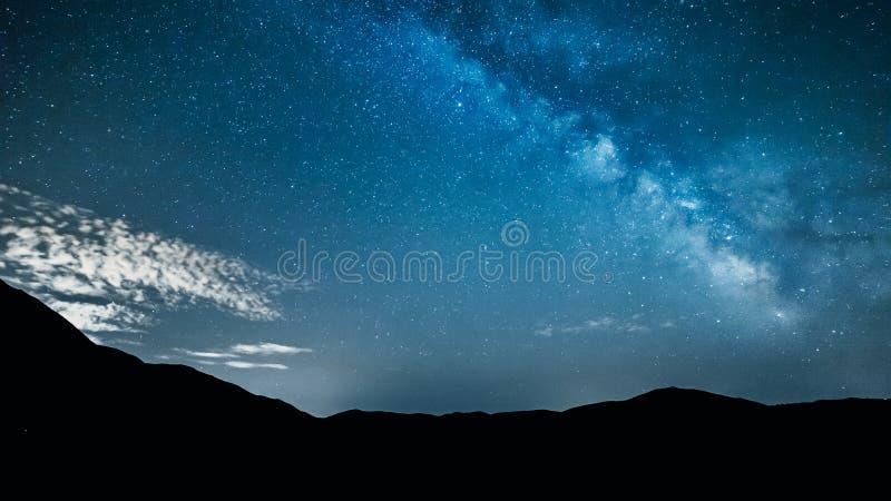 Αστέρια νυχτερινού ουρανού με το γαλακτώδη τρόπο πέρα από τα βουνά στοκ φωτογραφία